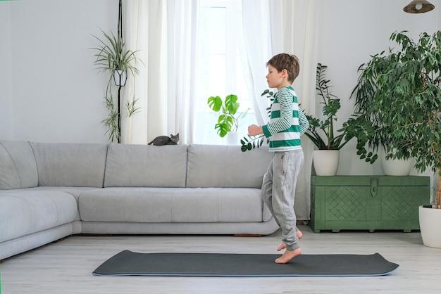 Le garçon avec un animal de compagnie fait du sport à la maison en ligne. l'enfant fait des exercices dans la pièce.
