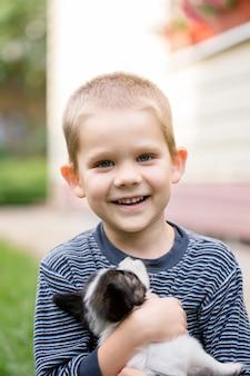 Un garçon avec un animal domestique dans le jardin