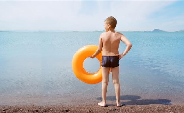 Garçon avec anneau flottant orange reste au bord de la mer et attend avec impatience