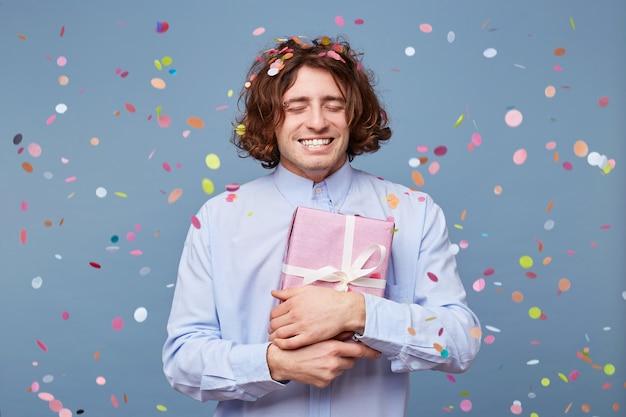 Garçon d'anniversaire avec les yeux fermés, appuie sur la boîte-cadeau attachée avec un ruban blanc à lui-même