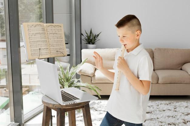 Garçon apprenant des cours en ligne à partir d'un ordinateur portable