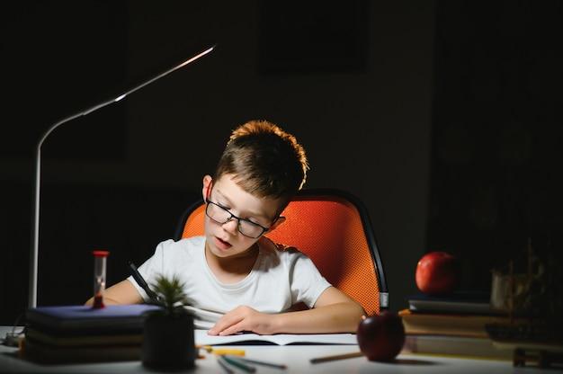Le garçon apprend des leçons à la maison à la table à la lumière d'une lampe de table.