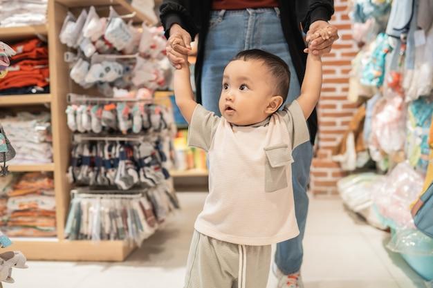 Le garçon apprend à marcher en faisant des emplettes dans le magasin de bébé