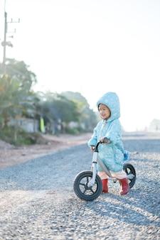 Un garçon asiatique âgé d'environ 1 an et 11 mois avec une veste d'hiver fait du vélo d'équilibre pour bébé