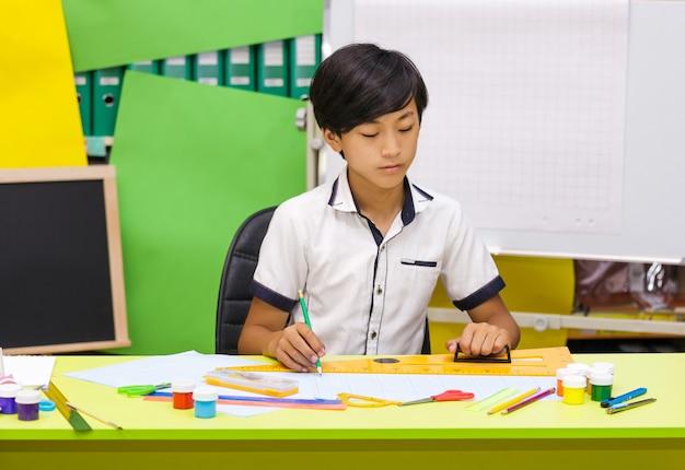 Garçon asiatique à l'aide d'une règle dans la salle de classe.