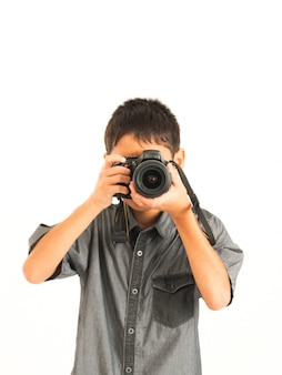 Garçon asiatique avec appareil photo reflex numérique sur fond blanc