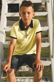 Garçon asiatique avec des cheveux dans les escaliers