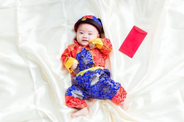 Garçon asiatique en costume chinois traditionnel sur fond blanc, concept du nouvel an chinois.
