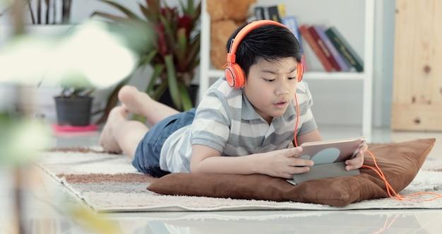 Garçon asiatique couché et jeu sur tablette numérique à la maison