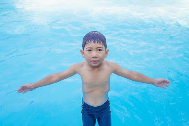 Garçon asiatique écarter les bras en jouant dans la piscine