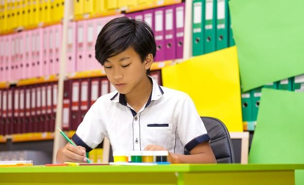 Garçon asiatique écrivant dans la salle de classe.