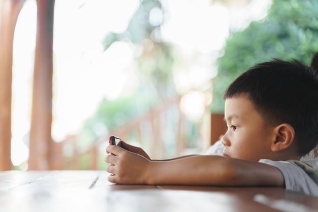 Garçon asiatique d'environ 3 ans et 10 mois accro et continue à utiliser un téléphone mobile