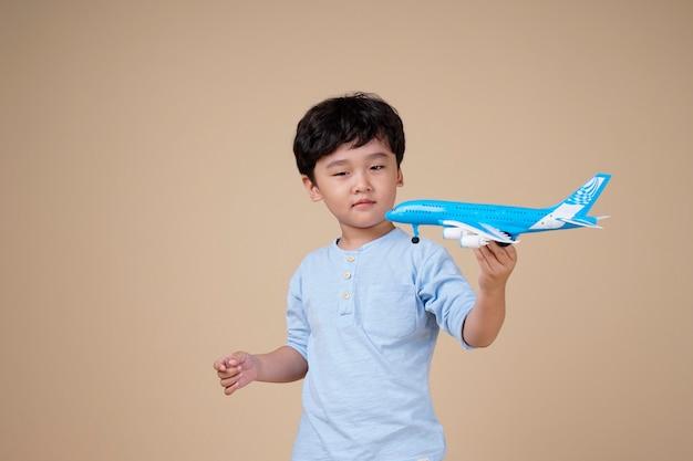 Garçon asiatique est excitant de voyager sur un jouet d'avion isolé sur beige