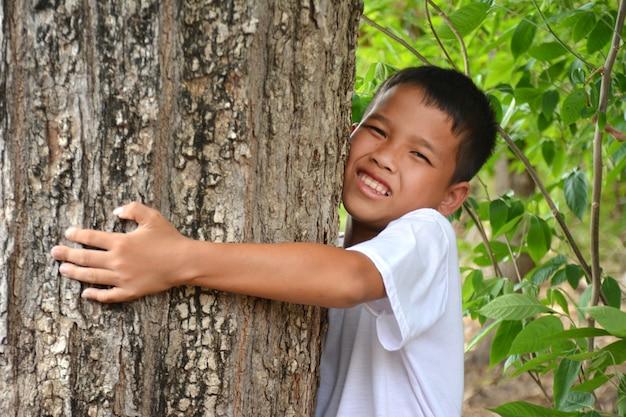 Garçon asiatique étreignant un arbre