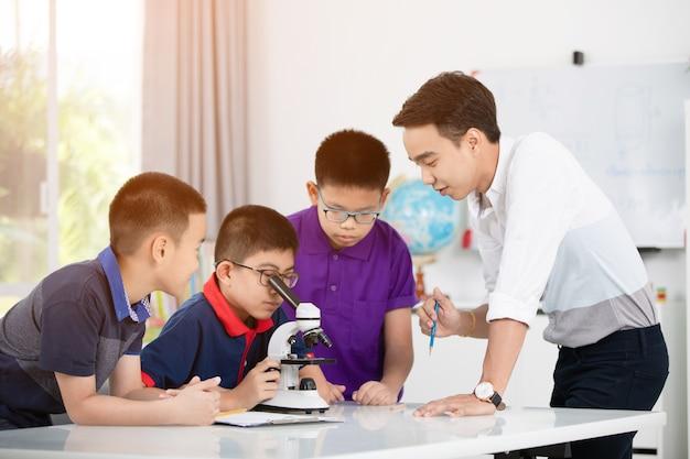 Garçon asiatique examinant la préparation sous le microscope