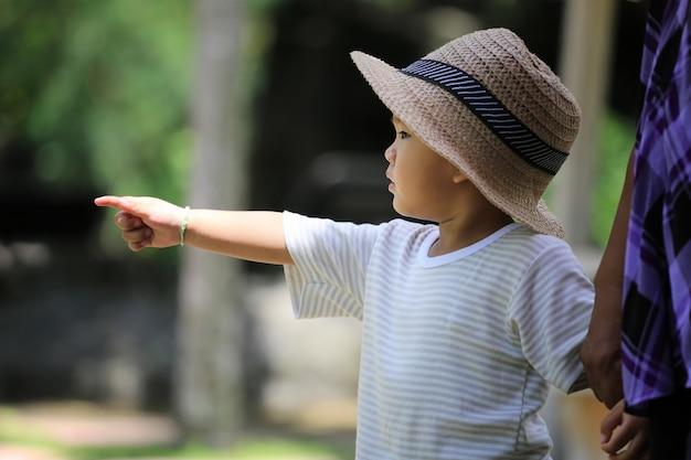 Un garçon asiatique a des intérêts au zoo.