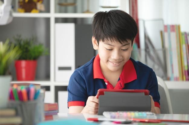Garçon asiatique, je regarde sur la tablette