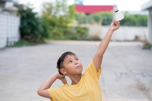 Garçon asiatique jouant au badminton à la maison