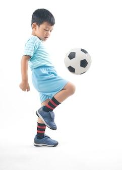 Garçon asiatique jouant au football isolé, enfant sain et fort