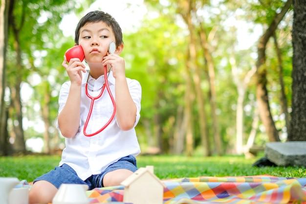 Garçon asiatique jouer docteur au parc naturel