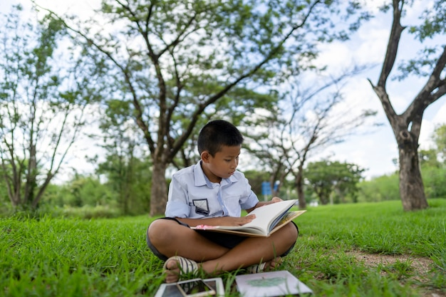 Un garçon asiatique lit un livre dans le parc.
