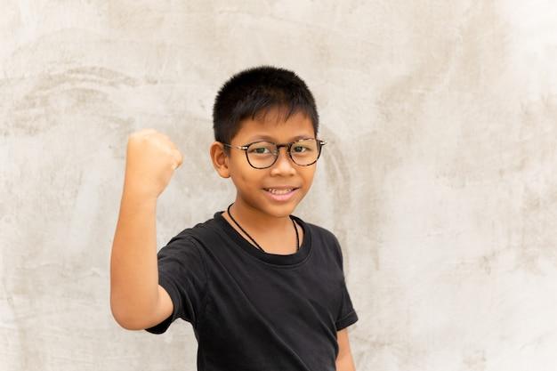 Garçon asiatique avec des lunettes mains et souriant sur fond gris.