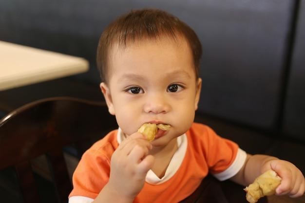 Un garçon asiatique mange du pain avec bonheur.
