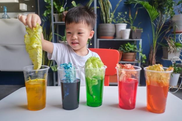 Garçon asiatique de la maternelle s'amusant à faire l'expérience du chou arc-en-ciel