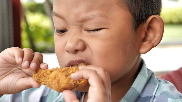 Un garçon asiatique mignon est heureux de manger une cuisse de poulet frit au restaurant.