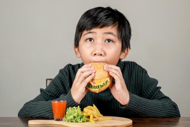 Garçon asiatique mignon mangeant un délicieux hamburger avec bonheur