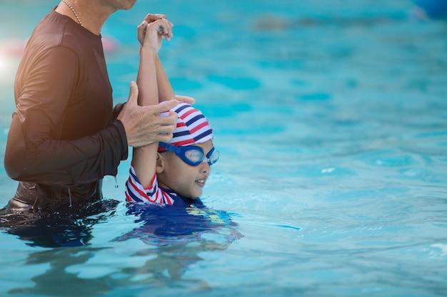 Garçon asiatique nager avec entraîneur dans la piscine