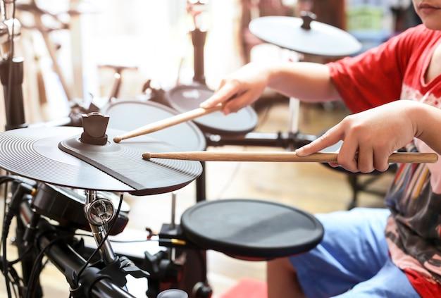 Un garçon asiatique non identifié joue un tambour électronique à tambour électronique