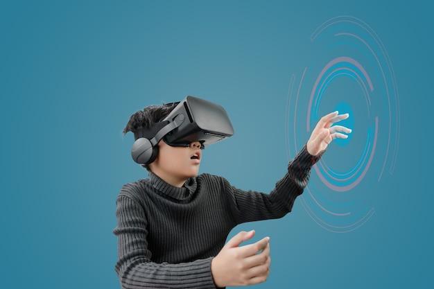 Garçon asiatique portant un casque de lunettes vr avec des graphiques technologiques devant sur fond bleu.