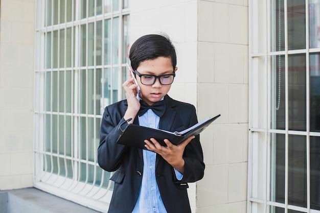 Garçon asiatique portant un costume noir vintage et des lunettes faisant appel par téléphone tout en lisant un carnet de notes