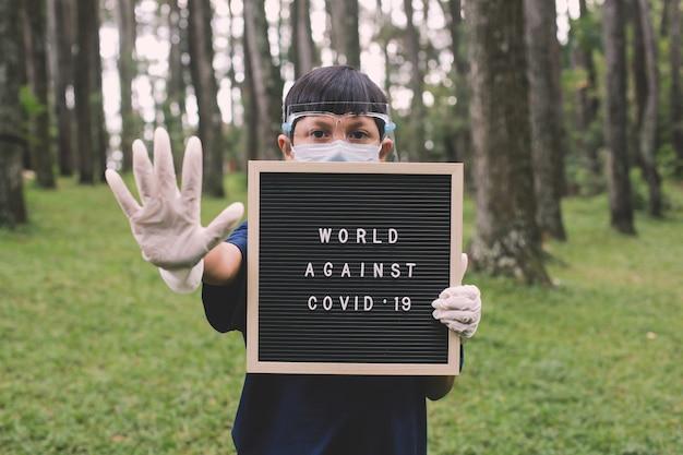 Garçon asiatique portant des masques faciaux et un gant en caoutchouc debout avec un geste d'arrêt de la main tout en maintenant le tableau des lettres
