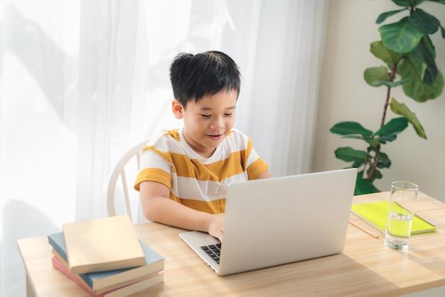 Un garçon asiatique préadolescent étudie en ligne sur un ordinateur portable avec un visage souriant et amusant à la maison. concept d'éducation en ligne et d'apprentissage en ligne.