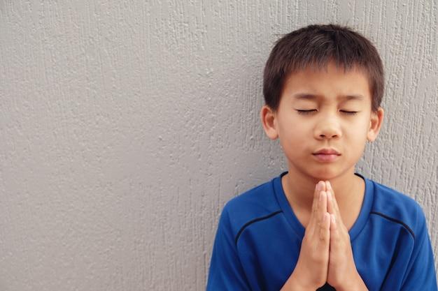 Garçon asiatique priant avec les yeux fermés