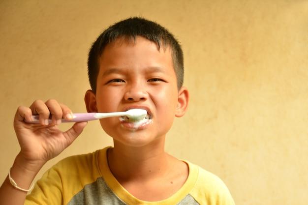 Garçon asiatique se brosser les dents dans la salle de bain