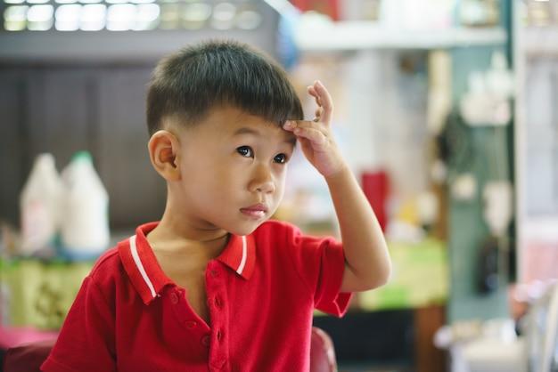 Garçon asiatique se faire couper les cheveux par coiffeur