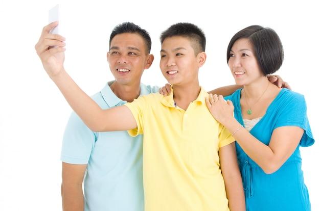 Garçon asiatique avec ses parents prenant selfie, à l'aide de smartphone