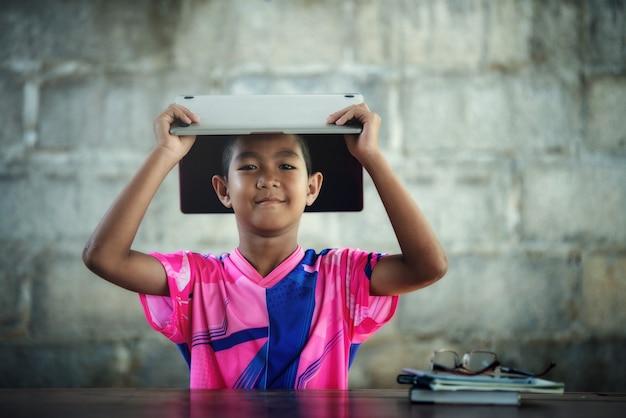 Garçon asiatique utilisant un ordinateur portable sur la table, revenez à l'école