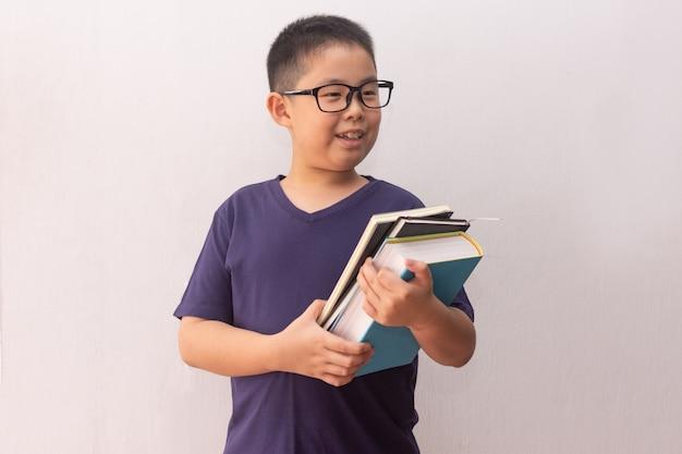 Garçon d'asie tenant des livres prêts pour l'école