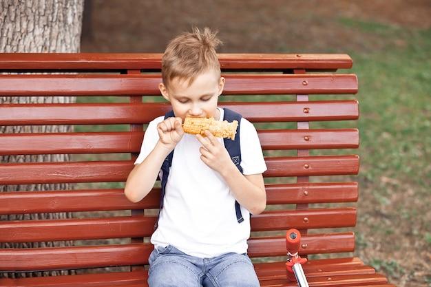 Garçon assis sur un banc en plein air dans un parc et mangeant du maïs bouilli frais.