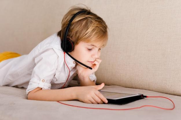 Garçon assis sur le canapé, manger du pop corn et jouer avec la manette de jeu pendant sa leçon en ligne à la maison, distance sociale pendant la quarantaine, auto-isolement, concept d'éducation en ligne