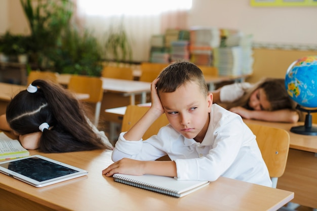 Garçon assis en classe en détournant les yeux