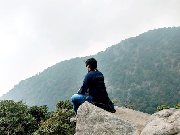Un garçon assis sur les collines de la montagne
