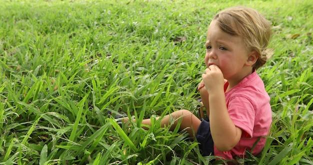Garçon assis dans l'herbe à l'extérieur. il porte une chemise rouge vue de côté