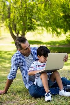 Garçon assis sur les genoux de son père et utilisant un ordinateur portable dans le parc
