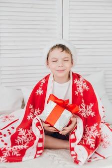 Garçon assis sur le lit et tenant une boîte avec un cadeau