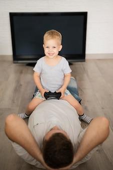 Garçon assis sur le père et jouant avec une manette de jeu